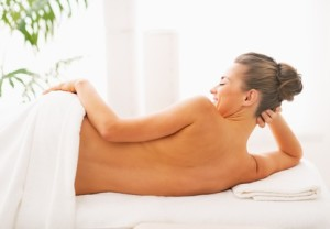 Smiling young woman laying on massage table. rear view